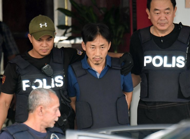 North Korean Ri Jong-chol, center, who was arrested in connection with the death of Kim Jong Un's half-brother, is transferred from Sepang district police station in Sepang, Malaysia Friday, March 3, 2017. AP