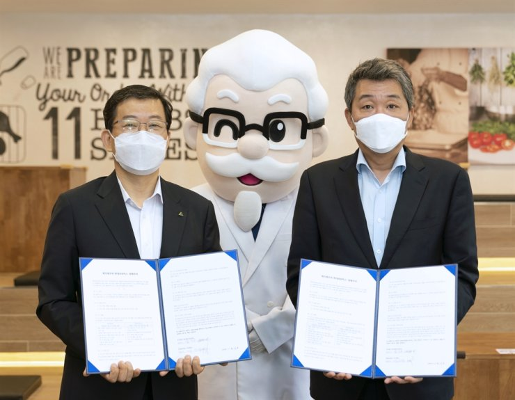 Hyundai Robotics Chief Operating Officer Seo Yoo-seong, left, poses with KFC Korea CEO Eom Ik-soo after they signed an MOU on developing automated process to cook chickens by using robots at an KFC outlet in Seoul, Friday. Courtesy of Hyundai Robotics