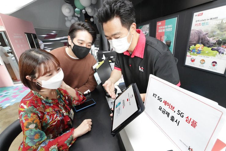 A KT employee explains the newly launched KT Simple 5G data plan to a customer at a KT authorized dealer store in Seoul, Monday. / Courtesy of KT