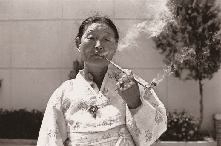 A woman smokes through a long, slender pipe called