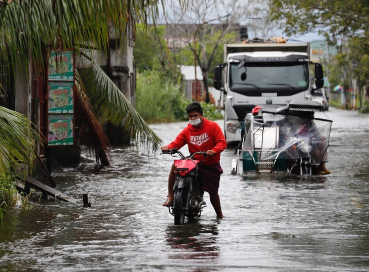 Motorists wade on a flooded road in the town of Macabebe, Pampanga province, Philippines, Oct. 26, 2020. According to reports, thousands of villagers were placed in evacuation centers as Typhoon Molave barreled through Southern Luzon island on Oct. 25. EPA