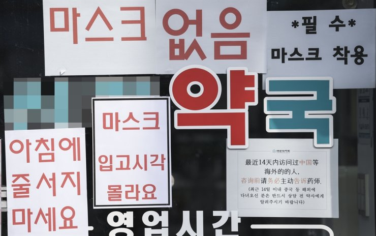 Multiple signs are posted on a pharmacy window in Yeongdeungpo-gu, Seoul, to indicate that face masks are out of stock and urge customers not to wait in line from early morning, March 9, when a five-day rotation system was implemented for face mask purchases. / Korea Times file