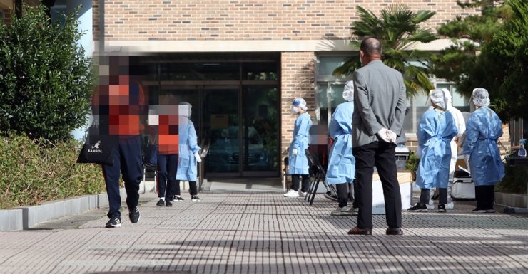 Students at a middle school in Gwangju's Gwangsan District go through a COVID-19 infection test, Friday, after one of the students was tested positive to the coronavirus as a result of local cluster infections. Yonhap