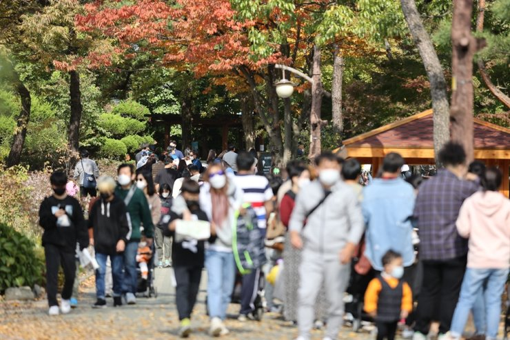 Seoul Grand Park, one of the biggest in the Seoul metropolitan area, is crowded with people, Sunday, on the first weekend after the government lowered social distancing guidelines from Level 2 to Level 1, Oct. 12. But concerns still remain as sporadic COVID-19 infection clusters have continued to be reported across the country. / Yonhap