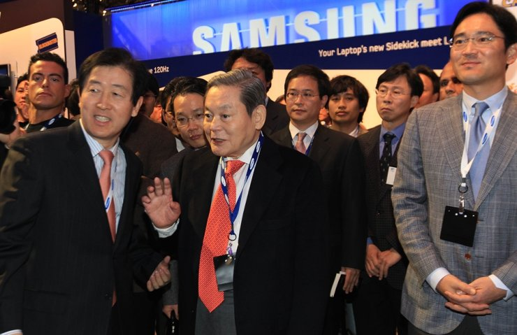 In this January 2010 file photo, Samsung Group's Chairman Lee Kun-hee, center, appears at the company's booth at the Consumer Electronics Show held in Las Vegas along with his son Jae-yong, right. The chairman passed away Sunday at age 78. / Yonhap