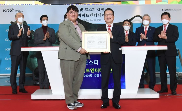 Big Hit Entertainment founder and CEO Bang Si-hyuk, left, poses for a photo with Korea Exchange CEO Jung Ji-won during a ceremony held to commemorate the entertainment company's listing on the stock market, Thursday, Seoul. / Yonhap