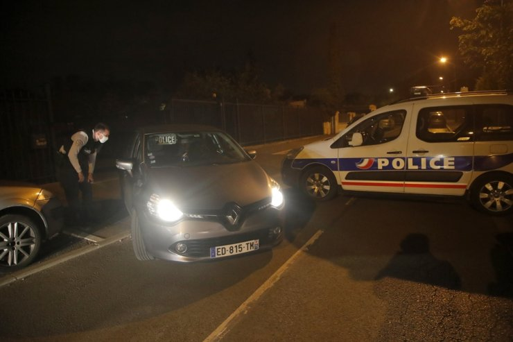 Police officers block access to a road after a history teacher who opened a discussion with students on caricatures of Islam's Prophet Muhammad was decapitated on a street in Conflans-Saint-Honorine, north of Paris, Friday. Police shot the suspected killer dead the same day. AP