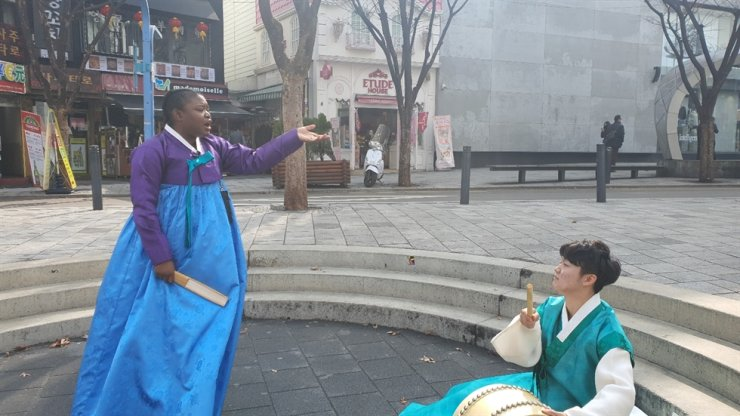 Laure Mafo, left, sings during a street performance of pansori. Courtesy of Laure Mafo