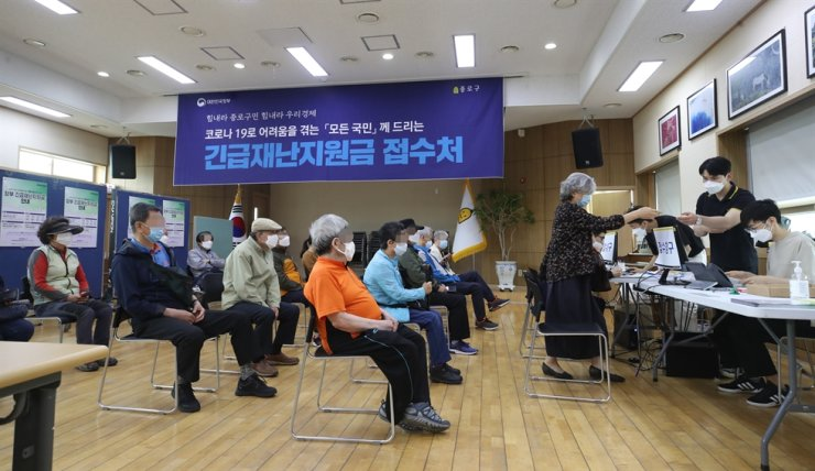 Senior citizens wait to register for the emergency relief fund in person at a community service center in Jongno-gu, Seoul, May 18. / Yonhap