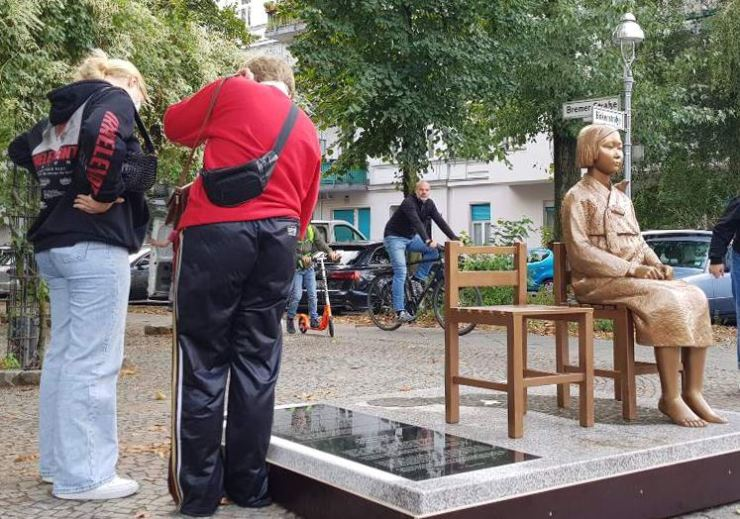 People read the epitaph of the Statue of Peace installed in the central Mitte district, Berlin, in this Sept. 27 photo. / Yonhap