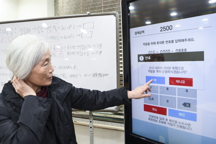 An elderly woman engages in a digital education program for senior citizens on using kiosks provided by Seocho District Office, Seoul, in this Nov. 13, 2019, photo. / Korea Times file
