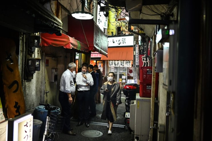 A woman wearing a mask walks past two men smoking at an alley by a street in Tokyo on Oct. 21, 2020. AFP