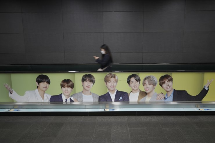 A woman rides an escalator near a commercial poster showing K-pop group BTS at a subway station in Seoul, Oct. 15, 2020. AP