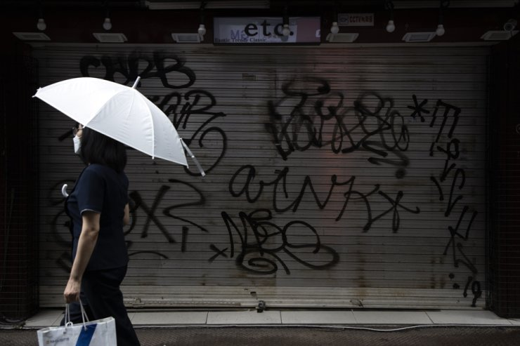 In this July 23, 2020, file photo, a woman wearing a mask walks past a closed shop at Myeongdong, which was a popular tourist area in Seoul before the COVID-19 pandemic. Korea Times photo by Choi Won-suk