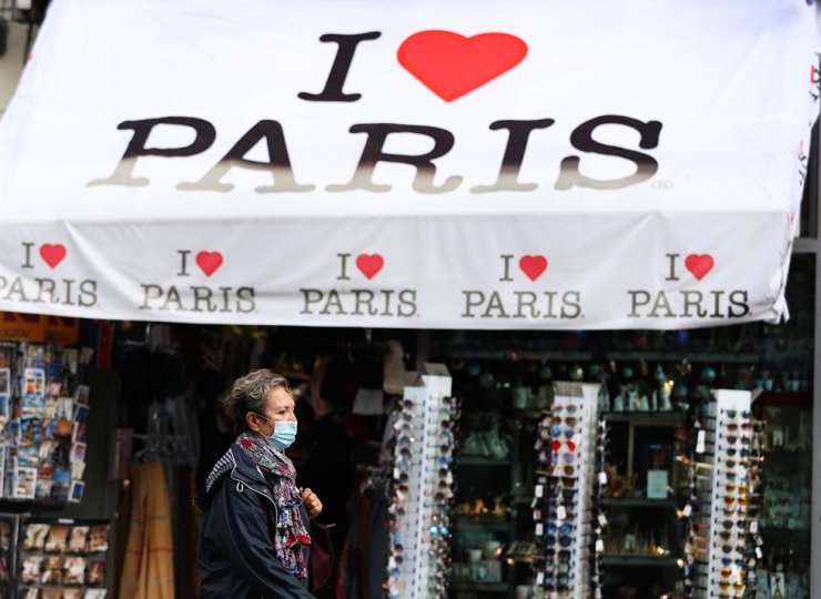 A woman wearing a face mask walks past a souvenir shop in Paris, France, Oct. 14, 2020. /Xinhua