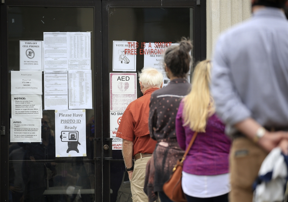 Voters wait in line, socially distanced from each other, to cast their early ballots at the Lemon City Branch Library precinct on October 19, 2020 in Miami, Florida. /AFP