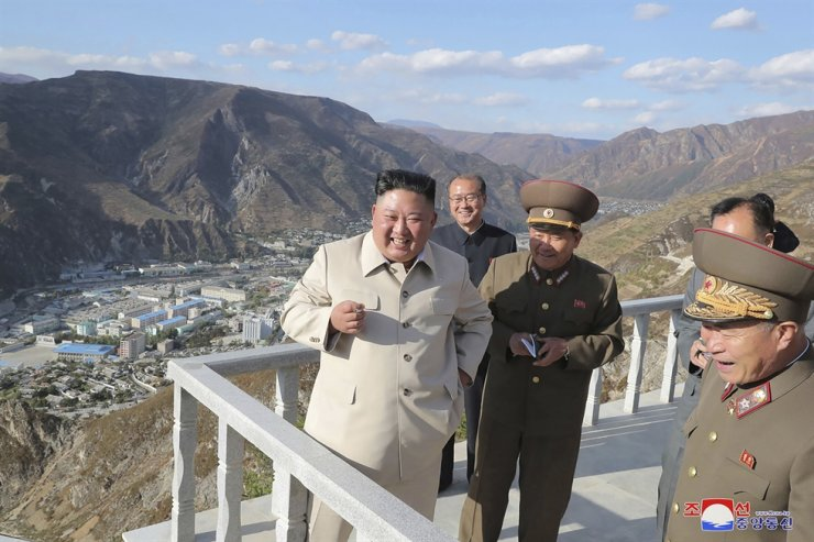 In this undated photo provided on Oct. 14, 2020, North Korean leader Kim Jong-un, left, visits the typhoon-ravaged rural town of Komdok, North Korea, to inspect recovery works. AP