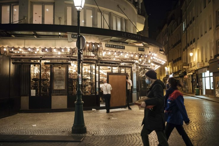 Waiters close a bar terrace in Paris, Saturday, Oct. 17, 2020. French restaurants, cinemas and theaters are trying to figure out how to survive a new curfew aimed at stemming the flow of record new coronavirus infections. AP