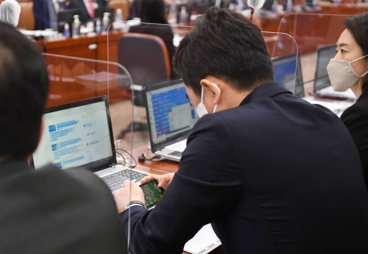 Rep. Kang Hoon-sik of the ruling Democratic Party of Korea plays a mobile phone game during a session of the National Assembly Trade, Industry, Energy, SMEs and Startups Committee's audit of the Ministry of Trade, Industry and Energy, at the Assembly, Thursday. Korea Times photo by Oh Dae-geun