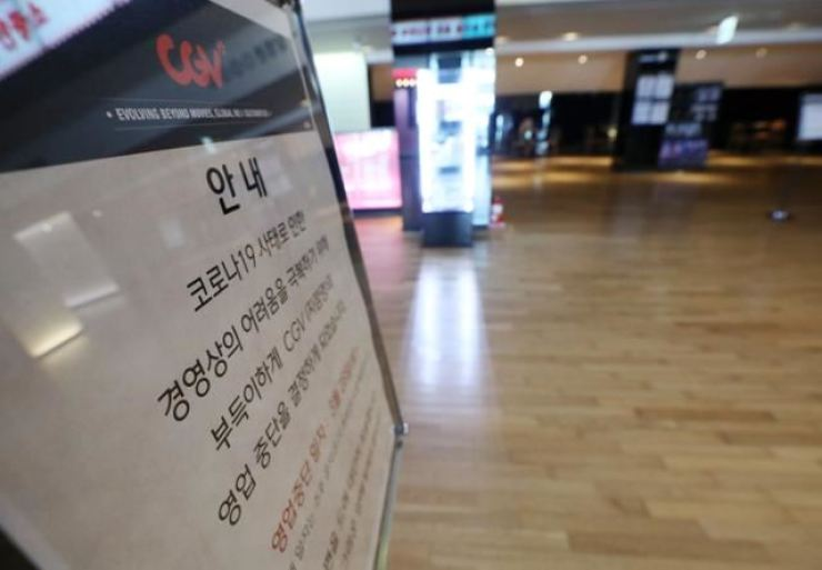 A sign on display at CGV Myeongdong Branch advises the suspension of business due to the prolonged fallout from COVID-19 pandemic, in this March file photo. / Korea Times file