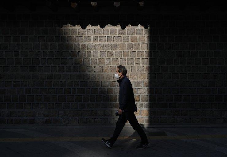 A man wearing a face mask walks along a wall outside the Deoksu Palace in Seoul, Tuesday, Oct. 20, 2020. AP