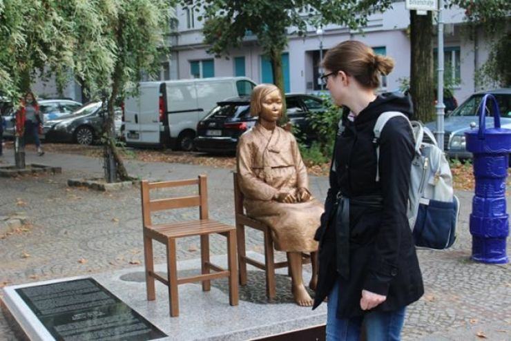 A woman walks past the statue of a girl symbolizing Korean victims of Japan's wartime sexual slavery in Berlin, in this file photo. Yonhap