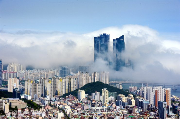Ocean fog sweeps over skyscrapers at Busan's Marine City in Haeundae in this July, 2016, file photo. Korea Times file
