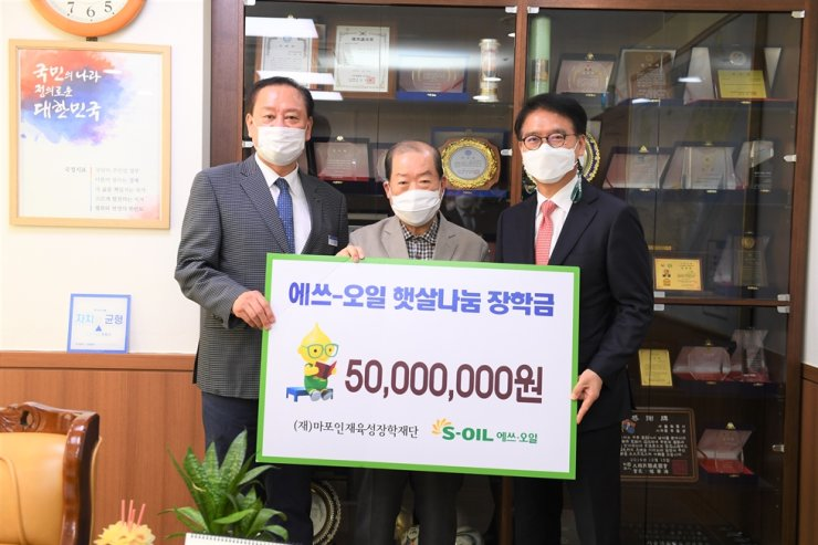 S-Oil President Ryu Yul, right, poses with Mapo Scholarship Foundation Chairman Park Hong-seop, center, and Mapo District Office head Yoo Dong-gyun after donating 50 million won to the foundation at the district office in Seoul, Thursday. S-Oil has been donating money for students of low income families in the district since 2017. Courtesy of S-Oil