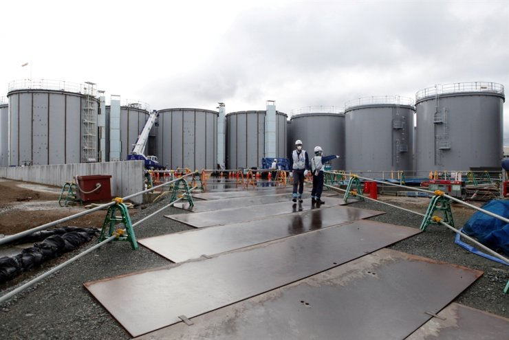 Workers stand near storage tanks for radioactive water at Tokyo Electric Power Co's (TEPCO) tsunami-crippled Fukushima Daiichi nuclear power plant in Okuma town, Fukushima prefecture, Japan January 15, 2020. REUTERS-Yonhap