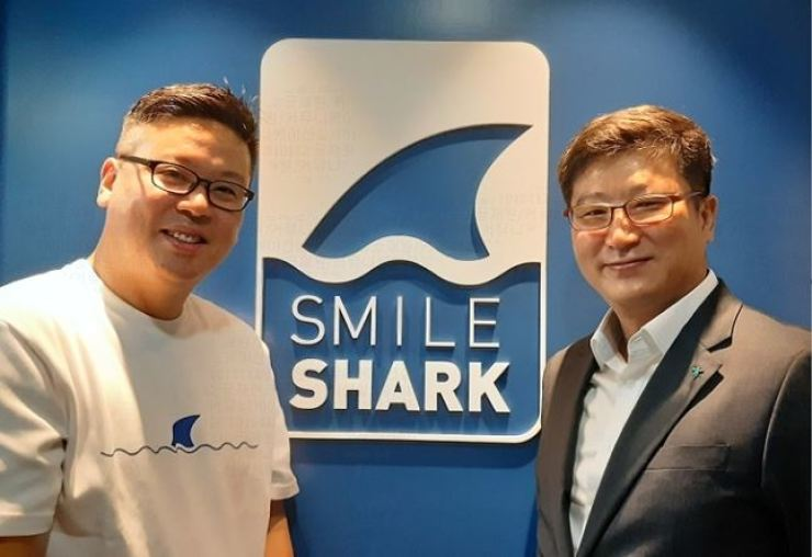 Hana Card head of global and new growth business division Han Kyung-ho, right, and cloud venture company Smile Shark founder Chang Jin-hwan smile during a business partnership ceremony at the Smile Shark headquarters in Seoul on Sept. 28. Hana Card has launched an email-invoice billing service, aimed at simplifying exporter companies' payment processes. Smile Shark will be the first company using the service. / Courtesy of Hana Card