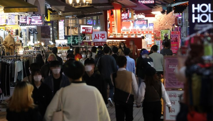 A street in Hongdae, one of the busiest entertainment districts in Seoul, is crowded with people after the government eased social distancing rules imposed to counter the COVID-19 pandemic, in this Oct. 12 photo. Yonhap