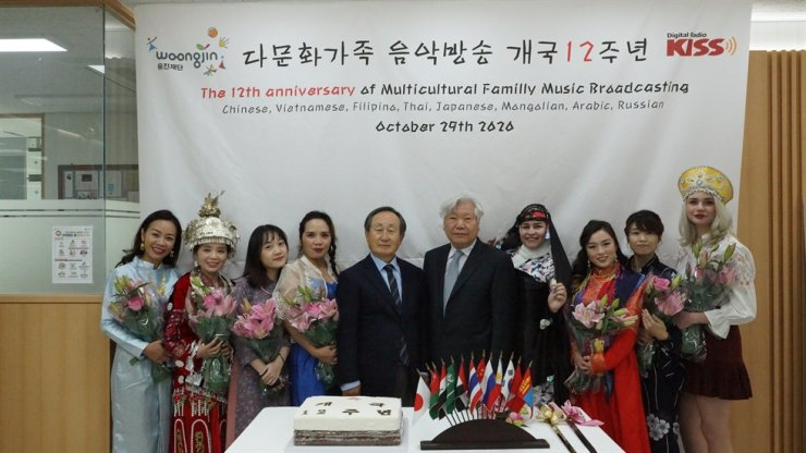 Hosts of the Multicultural Family Music Broadcasting Service pose for a photo with Woongjin Foundation Chairman Shin Hyun-woong, fifth from left, and cable network Digital Skynet President Kim Choong-hyun, sixth from left, for the service's 12th anniversary event at the broadcasting studio in Seoul, Thursday. Courtesy of Woongjin Foundation