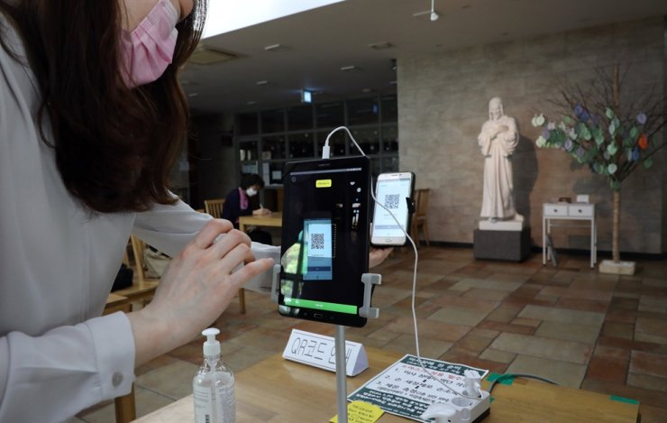A church-goer scans her QR code to register her personal information as a condition of entry to a Catholic church in Songpa-gu, Seoul, June 17. Such QR code schemes are part of the government's contact tracing efforts amid the COVID-19 pandemic. / Yonhap