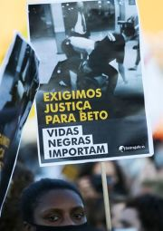 A woman protests against racism, after Joao Alberto Silveira Freitas was beaten to death by security guards at a Carrefour supermarket in Porto Alegre, Brazil, November 20, 2020. Sign reads: 'Black lives matter' and 'We demand justice for Beto.' REUTERS-Yonhap