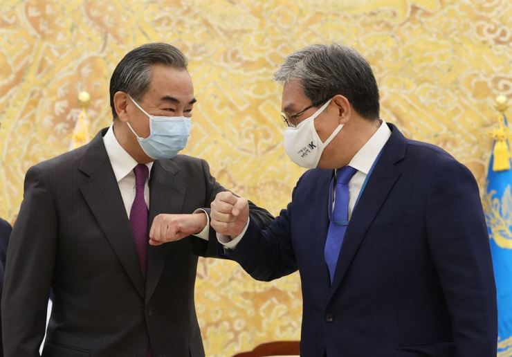 Presidential chief of staff Noh Young-min, right, a former Korean ambassador to China, greets Chinese State Councilor and Foreign Minister Wang Yi at Cheong Wa Dae, Thursday. Yonhap