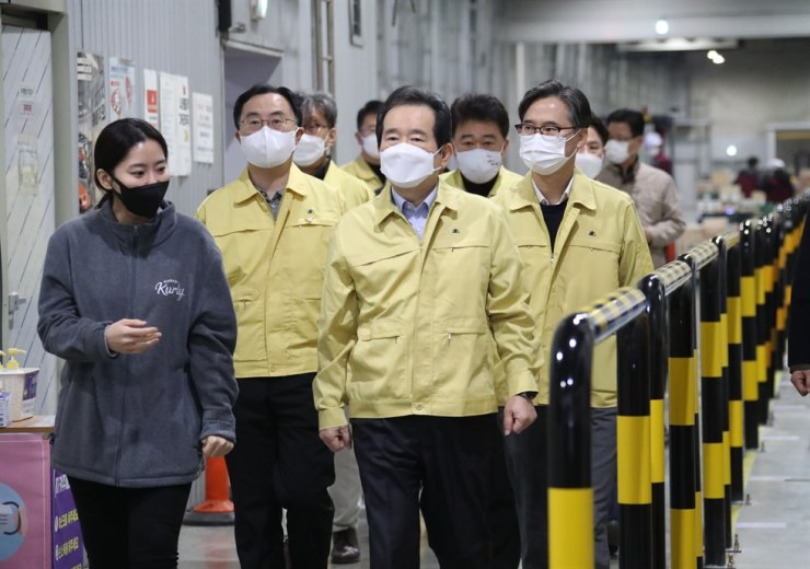 South Korean Prime Minister Chung Sye-kyun, third from left, listens to Market Kurly CEO Kim Seul-ah as he and his aides visited one of the online shopping company's delivery depots in Jangji area in Seoul's Songpa District to check the company's COVID-19 prevention measures on Nov. 21. Yonhap