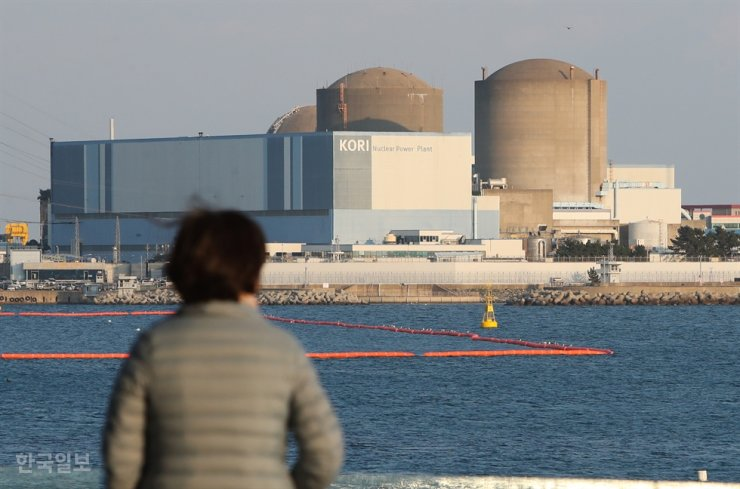 In this November 2017 photo, a woman looks at the Kori Nuclear Power Site in Busan's Gijang District. Korea Times file