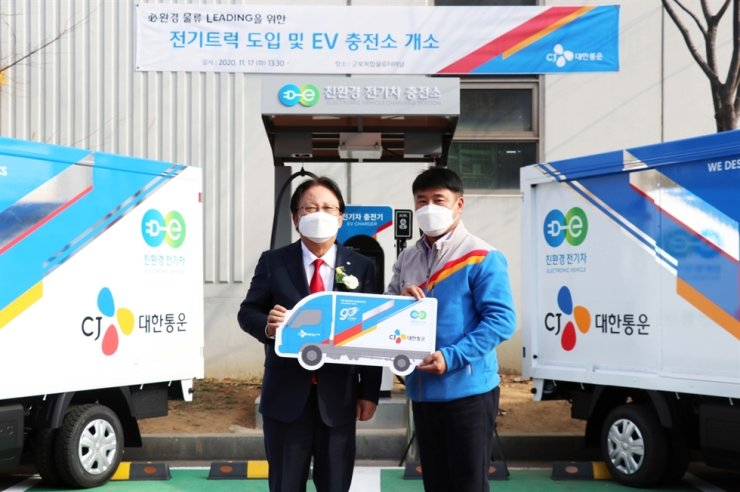 CJ Logistics CEO Park Keun-hee, left, poses for a picture with a delivery worker in front of the company's electric vehicle (EV) charging station in Seoul, Wednesday. CJ Logistics became the first local firm to use electric vehicles for delivery services. The firm also plans to expand its business through installing EV charging stations around the country.