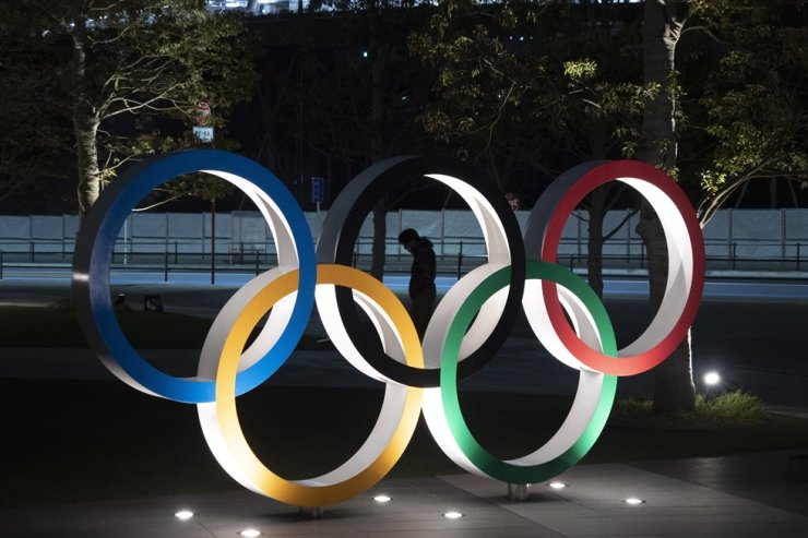 In this March 24, 2020, file photo, a man is seen through the Olympic rings in front of the New National Stadium in Tokyo. AP