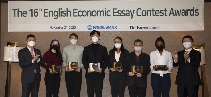 Korea Times President-Publisher Oh Young-jin, right, and Woori Bank CEO Kwon Kwang-seok, left, applaud after giving awards to the winners of the newspaper's 16th English Economic Essay Contest at the Lotte Hotel Seoul, Tuesday. From left are Kwon, Gabriela Bernal, Sven-Hendrik Arp, Jung Ho-joon, Maria Natasha Lintang, Park Han-dol's father who attended the event on behalf of his son, Leah Nangila Nabangi and Oh. Commendation award winner Joshua Chang was unable to attend the ceremony. / Korea Times photo by Choi Won-suk