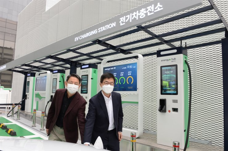 LG Electronics Chief Technology Officer I.P. Park, right, and Lee Sang-yong, head of the firm's automotive and business solutions center, pose while recharging an electric vehicle using a charger made by LG's EV management system at a GS Caltex EV charging station in Seoul, Nov. 18. / Courtesy of LG Electronics