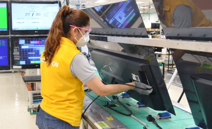 An LG Electronics employee works on an OLED TV production line at the company's factory in Mexico, Nov. 16. LG said it is operating its TV manufacturing lines at full capacity to meet the soaring demand for TVs in North America ahead of the year-end shopping bonanza. / Courtesy of LG Electronics