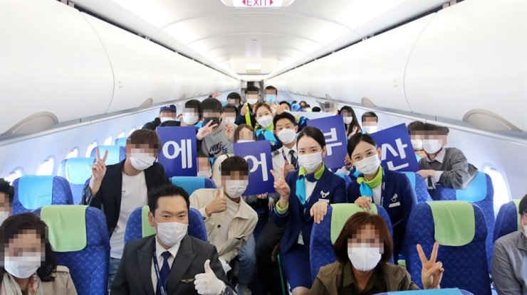 Passengers and crew members for 'a flight to nowhere' pose on an Air Busan plane, Oct. 31. Courtesy of Air Busan