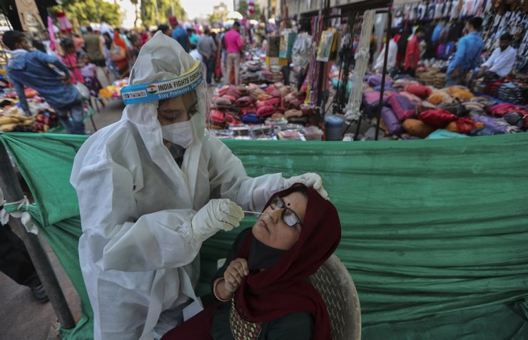 A health worker takes a nasal swab sample of a woman to test for COVID-19 at a facility erected in a market in Ahmedabad, India, Tuesday, Nov. 17, 2020. AP