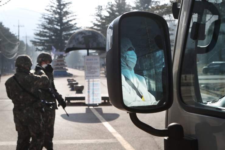 A bus to carry COVID-19 patients stands by in front of the boot camp of the Army's 5th Infantry Division in Yeoncheon, Gyeonggi Province, Thursday, as nearly 70 infections were reported there.