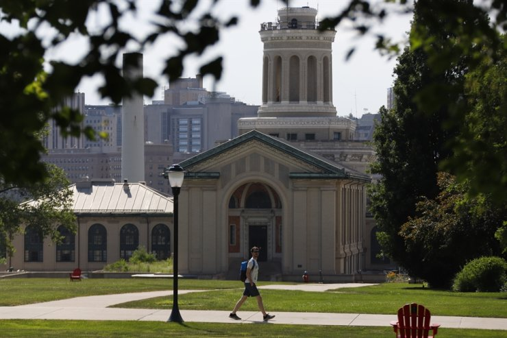 In this file photo from June 7, 2019, a man walks by Hamerschlag Hall on the Carnegie Mellon University campus in Pittsburgh. Colleges in the U.S. have seen a sharp enrollment drop among international students in the fall of 2020. University administrators say a number of hurdles and new policies brought on by the coronavirus pandemic are to blame. /AP