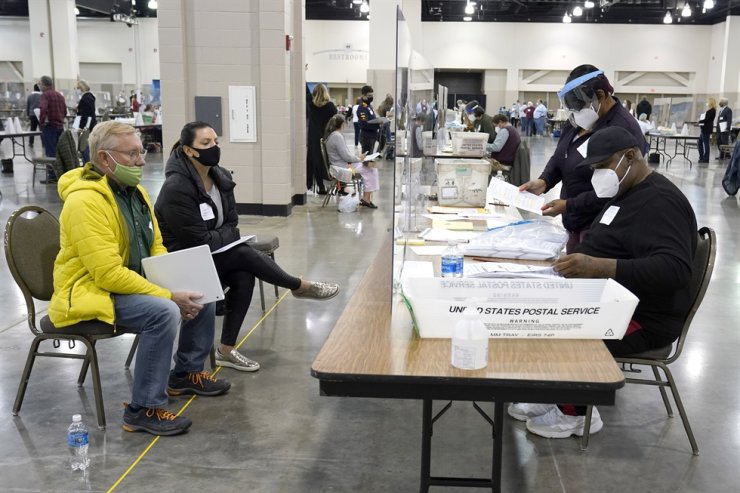 Election workers, right, verify ballots as recount observers, left, watch during a Milwaukee hand recount of presidential votes at the Wisconsin Center, Friday, Nov. 20. AP-Yonhap