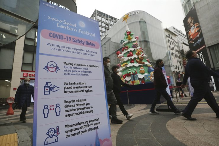 People wearing face masks walk past a Christmas tree set up for a year-end festival featuring colorful lanterns at a shopping street in Seoul, Friday, Nov. 20, 2020. AP