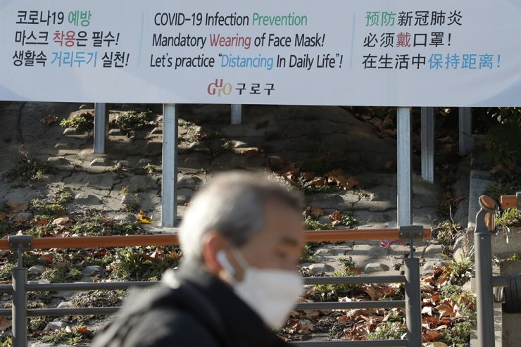 A man wearing a face mask walks past a banner showing precautions against the coronavirus in Seoul, Monday, Nov. 23, 2020. AP