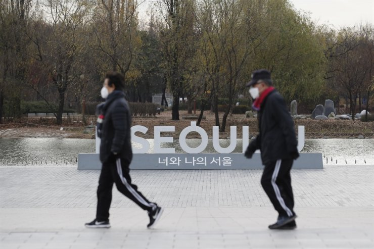 People wearing face masks walk past the display of the Seoul logo at a park in Seoul, Tuesday, Nov. 24, 2020. AP